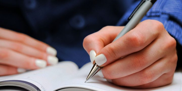 Women Hand with Pen Filling Out Form